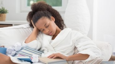 Black Woman Falling Asleep with a Book
